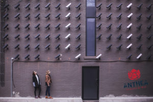 Security cameras on a wall staring at two women on the street